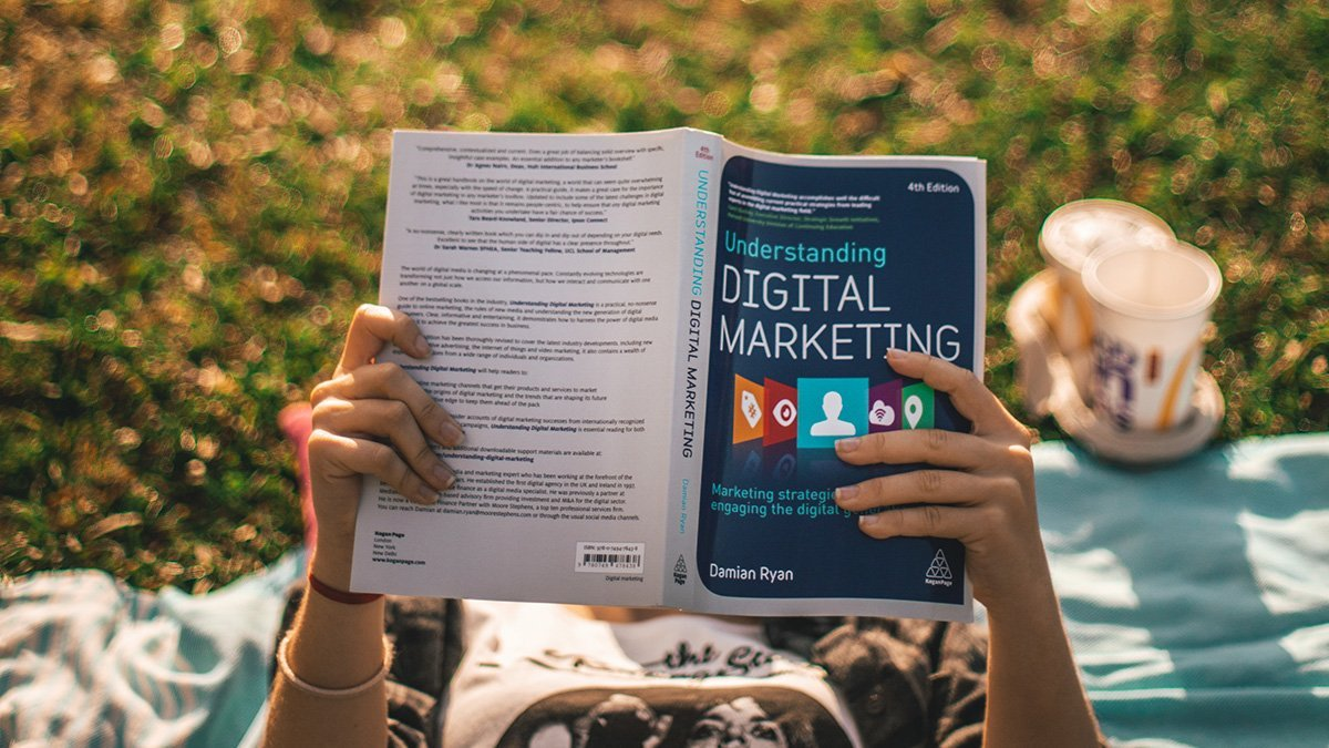 """A person is lying in the grass reading the book """"Understanding Digital Marketing."""""""