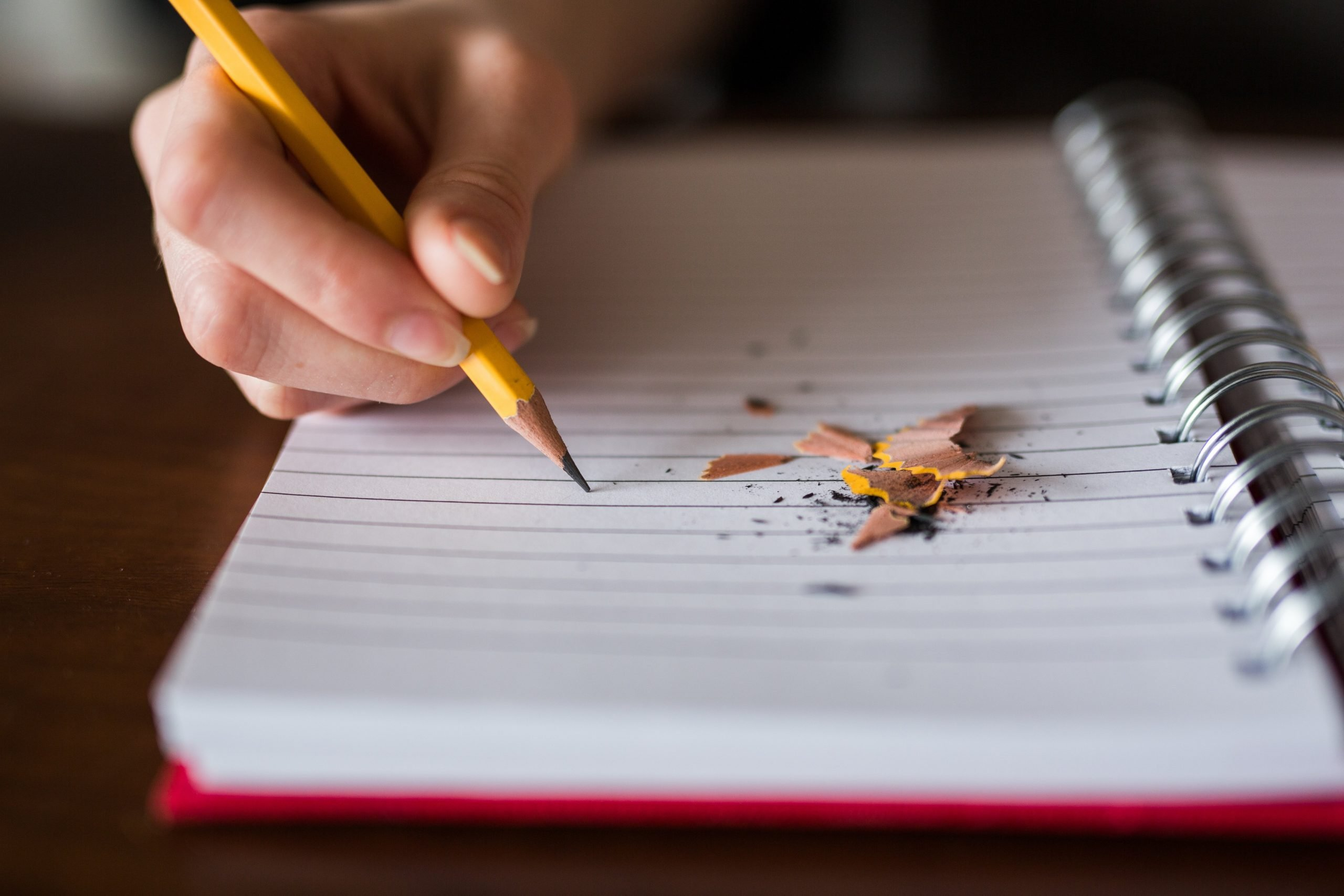 A closeup image of a person writing on lined paper with a pencil. Pencil shavings lie nearby.